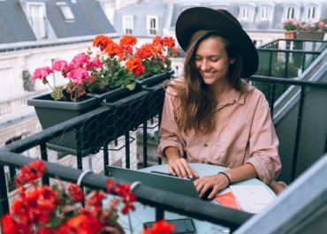 woman wearing beige dress shirt using laptop computer
